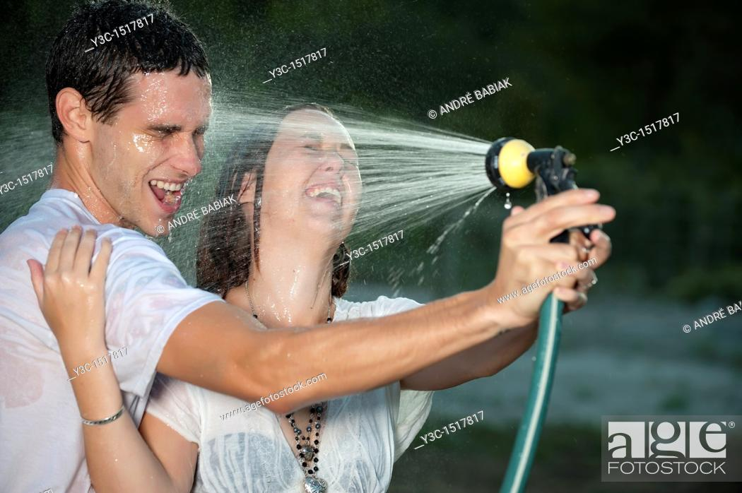 Stock Photo: Young couple getting wet with garden sprayer.