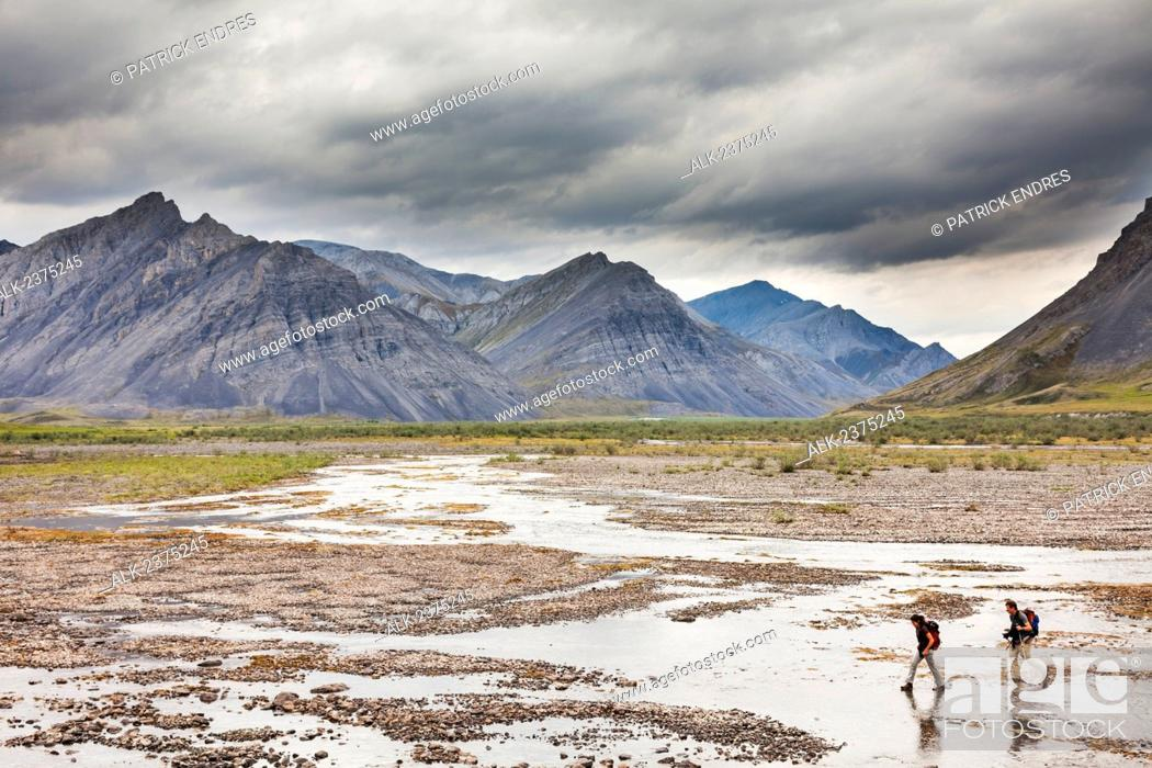 Stock Photo: Hikers cross the Marsh Fork of the Canning river which comprises the western border of the Arctic National Wildlife Refuge in the Brooks range mountains, Alaska.