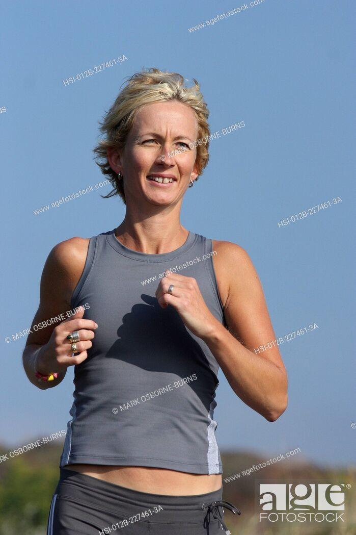 Stock Photo: Blonde woman outdoors. Jogging close-up.