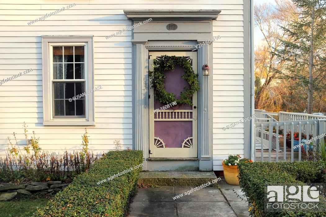 Stock Photo: The front door of an old house decorated with a holiday wreath, in the town of Sandwich, Cape Cod, Massachusetts, United States.