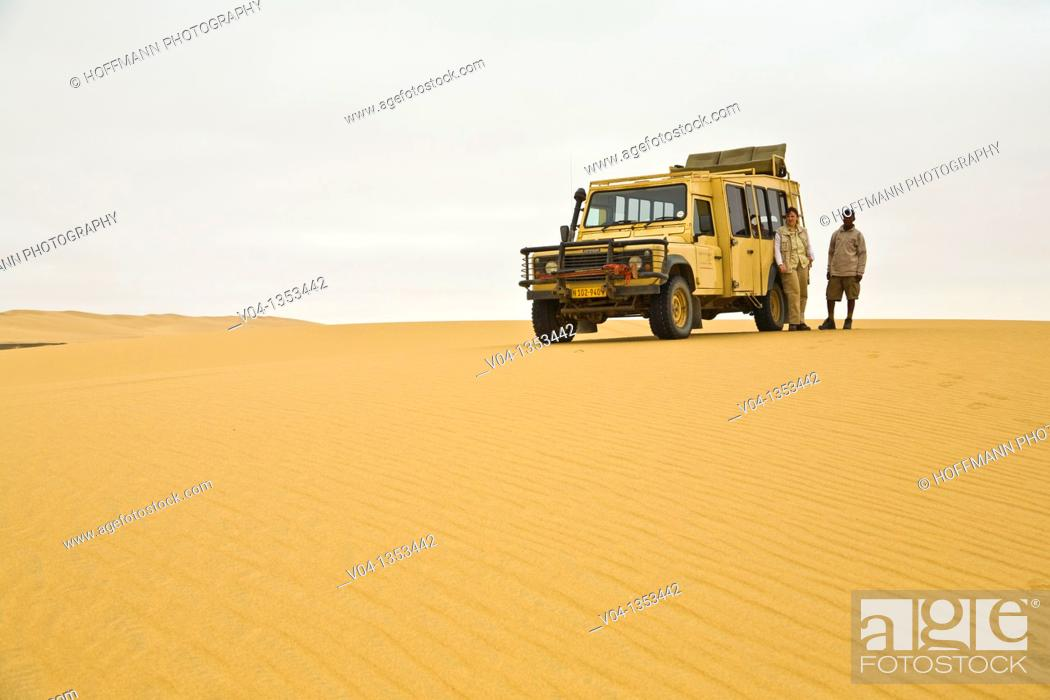 Stock Photo: A landrover and two people in the desert of the Skeleton Coast Park, Namibia, Africa.