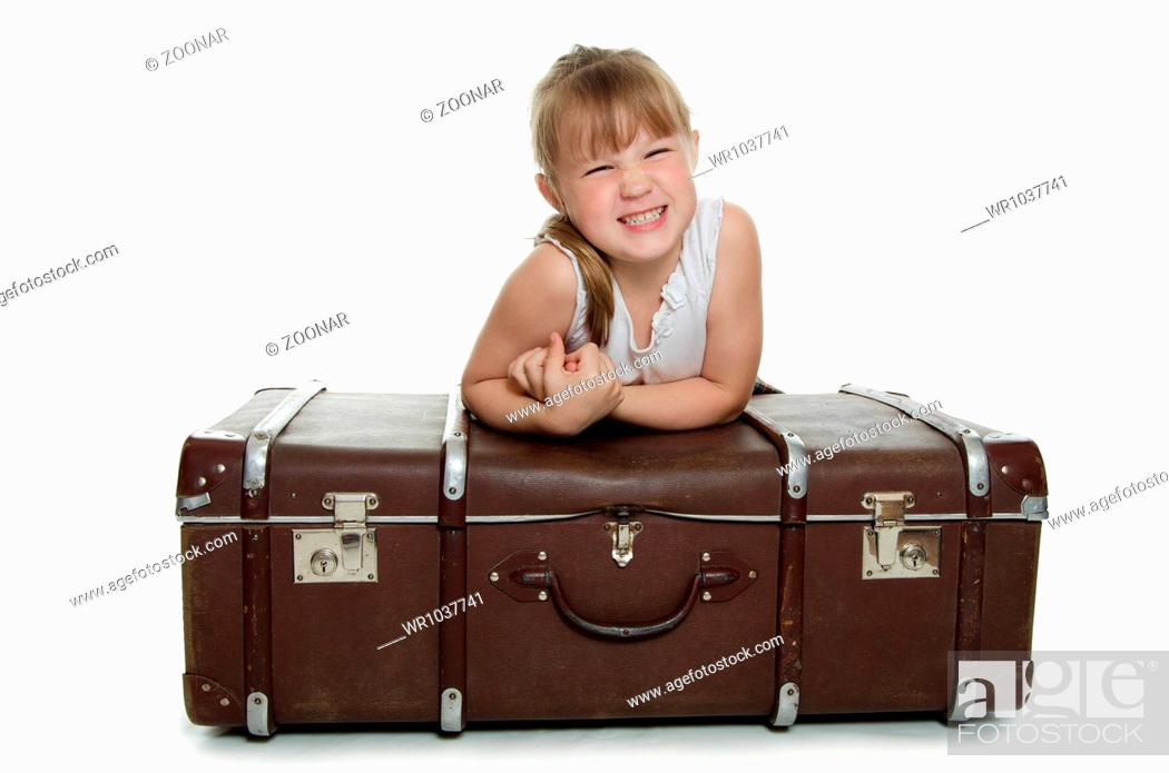 Imagen: The little girl on old suitcases.