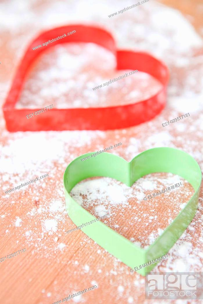 Stock Photo: Closeup of heart shaped gingerbread biscuit cutters and dough.