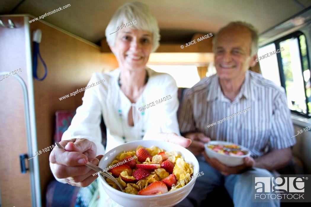 Stock Photo: Senior couple eating breakfast in back of camper van, smiling, close-up of bowl differential focus.