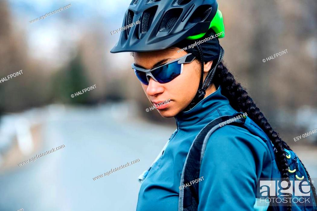 Imagen: Female mountain biker with sunglasses standing on road outdoors in winter.