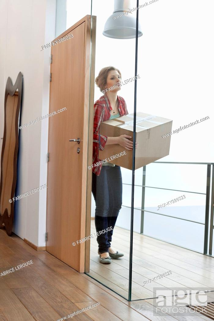 Stock Photo: Woman carrying a cardboard box at home.