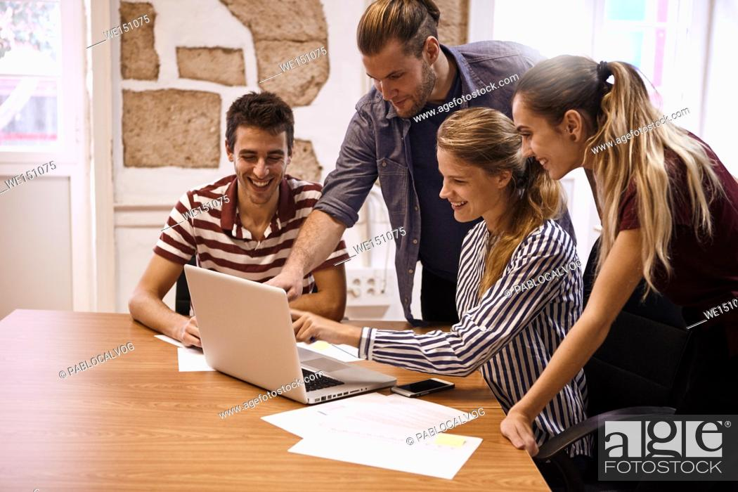 Stock Photo: Young business team in a meeting with one male and one female both pointing at the laptop they are all sharing while everyone is smiling.