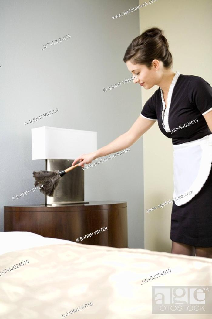 Stock Photo: Maid dusting night stand.