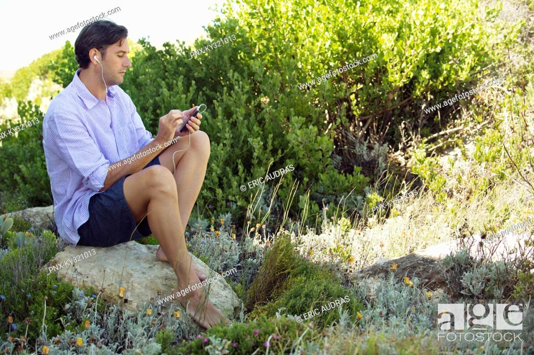 Stock Photo: Mid adult man sitting on a rock and listening to music with an MP3 player.
