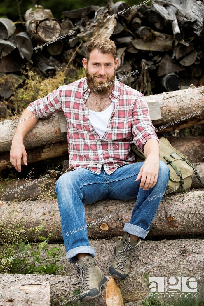 Stock Photo: Portrait of bearded man sitting on stack of wood.