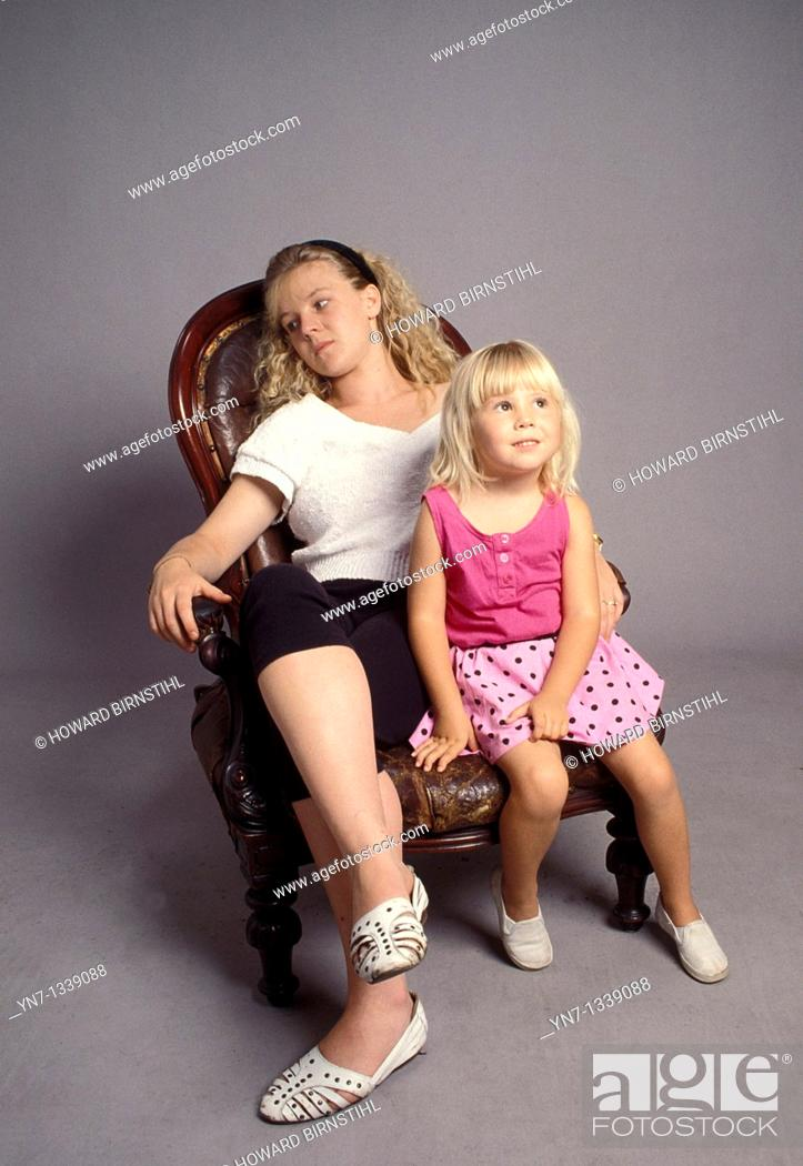 Stock Photo: mother and daughter relaxing on an old armchair.