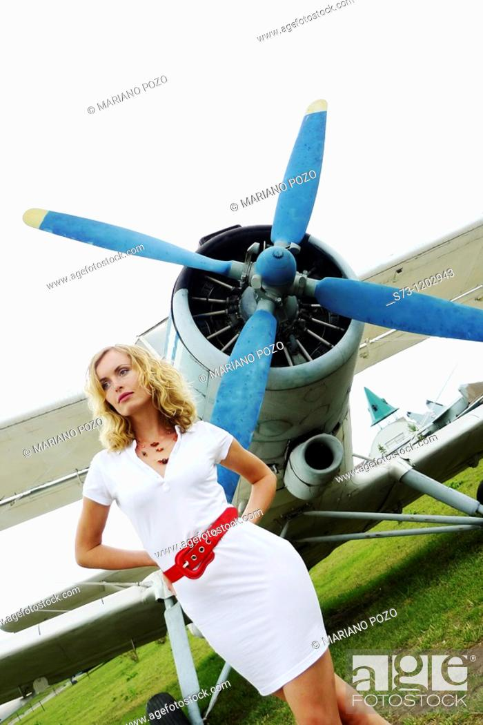Stock Photo: Young woman poses front a old aeroplane.