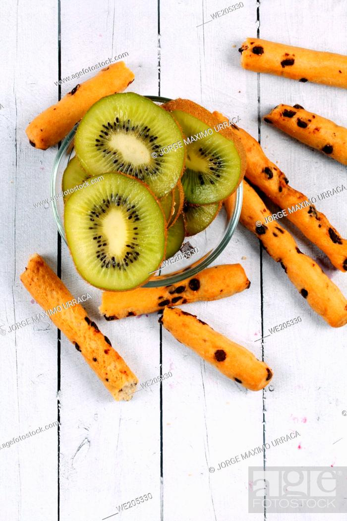 Stock Photo: Chocolate sticks with kiwi slices on a white wooden board.