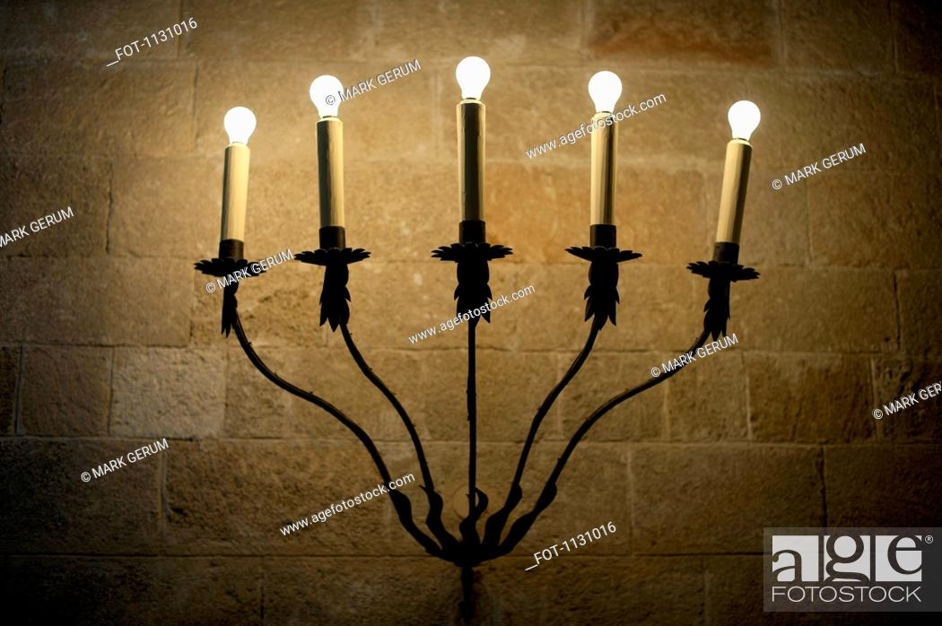 Stock Photo: A sconce with illuminated electric candles.
