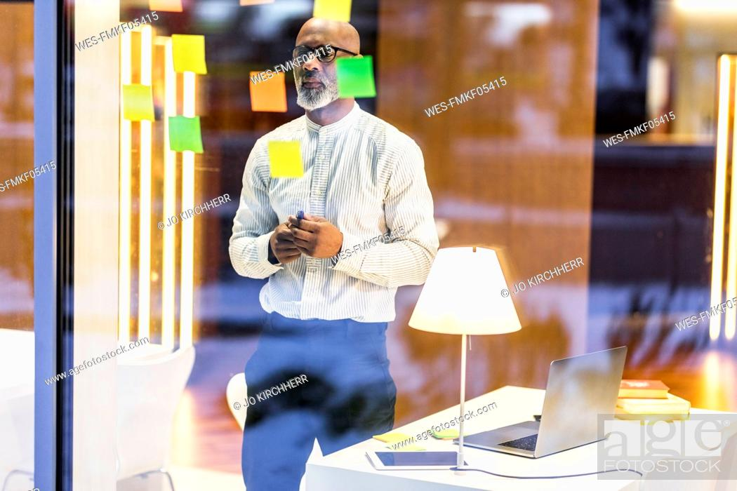 Stock Photo: Businessman looking at adhesive note glueing on windowpane.