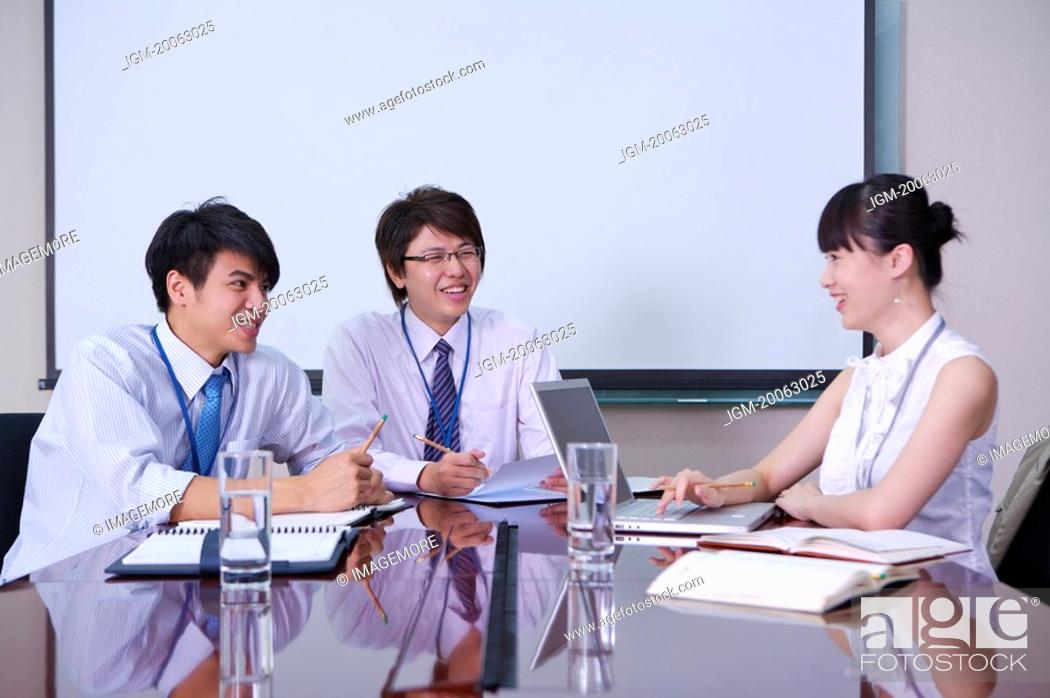 Stock Photo: Colleagues talking in office and smiling together.