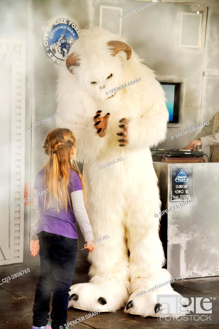 "Stock Photo: A furry creature in a fanciful costume greets a little girl at a winter """"snowfest"""" with artificial snow in Lake Forest, CA."