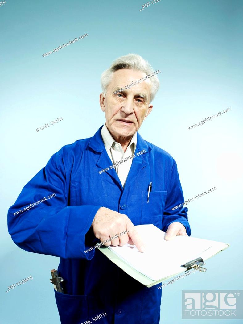 Stock Photo: A senior man wearing coveralls and pointing to a paperwork on a clipboard.