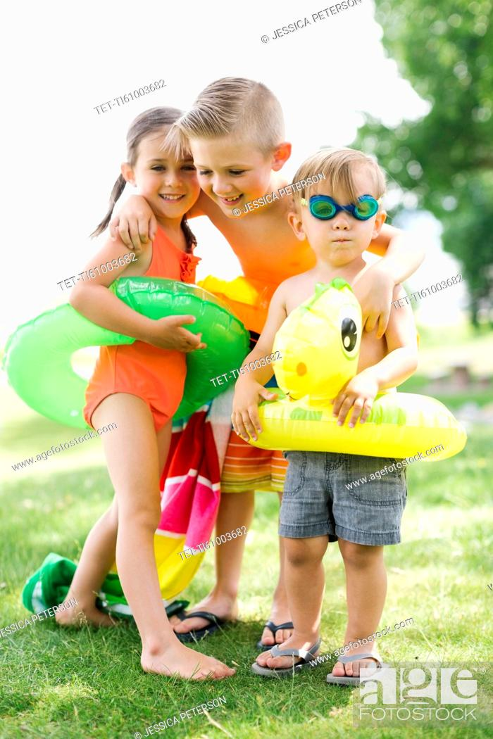 Stock Photo: Two boys (2-3, 6-7) and girl (4-5) standing with inflatable rings.