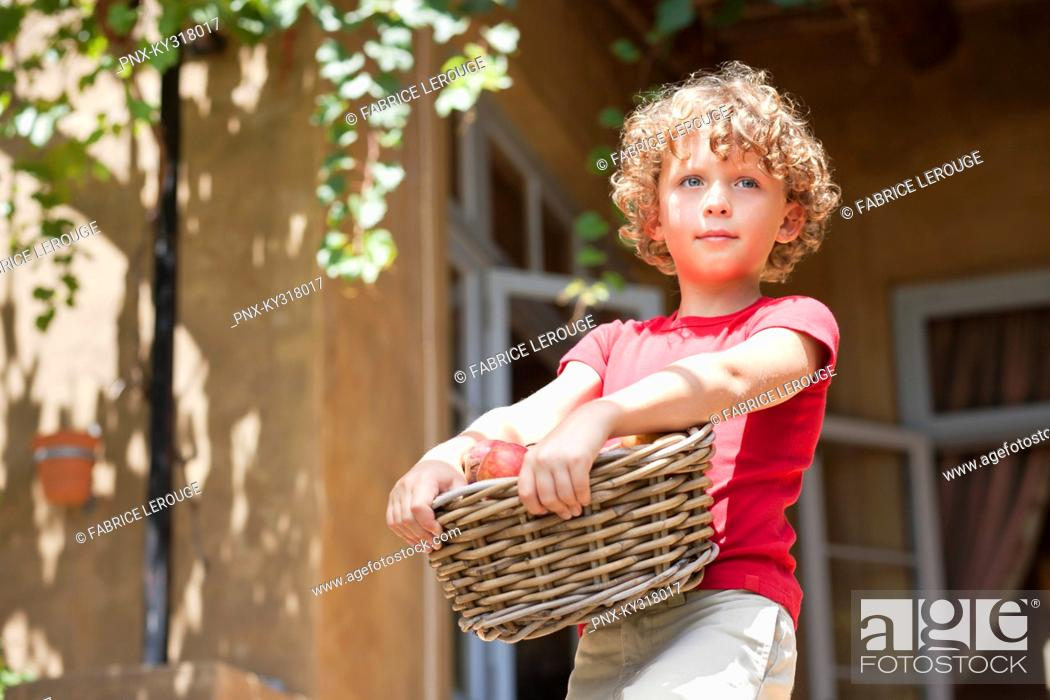 Stock Photo: Boy holding basket of apples.