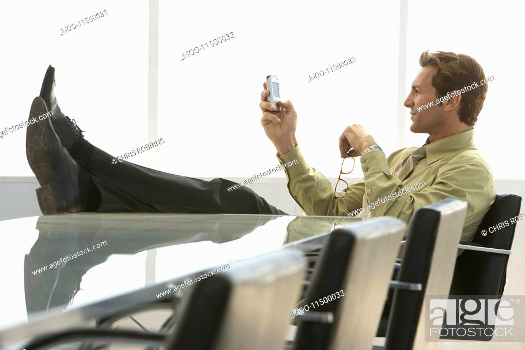 Stock Photo: Relaxed businessman with feet up text messaging on mobile phone in conference room.