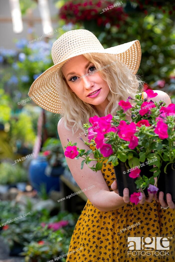 Stock Photo: A happy 30 year old blond woman shopping in a plant nursery holding potted petunias.
