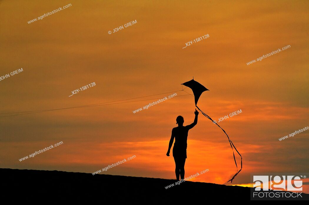 Stock Photo: Silhouette of a child flying a kite.
