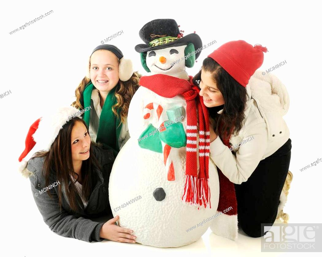 Stock Photo: Three young teen girls playing around a Christmas snowman. On a white background.
