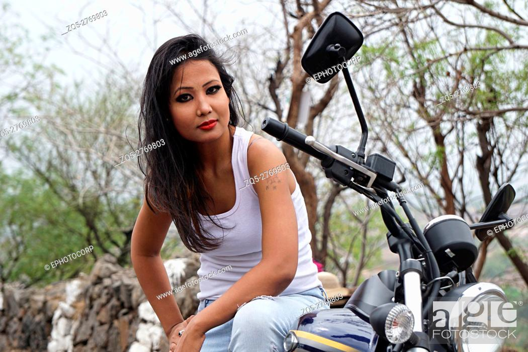 Stock Photo: Young woman with tattoo on arm sitting on a motorbike, Pune, Maharashtra.