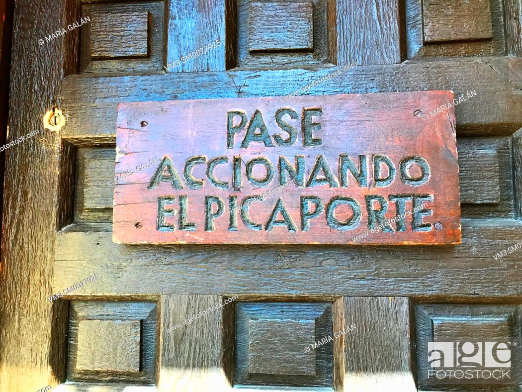 Stock Photo: Pase accionando el picaporte, wooden carved sign on door. Pedraza, Segovia province, Spain.