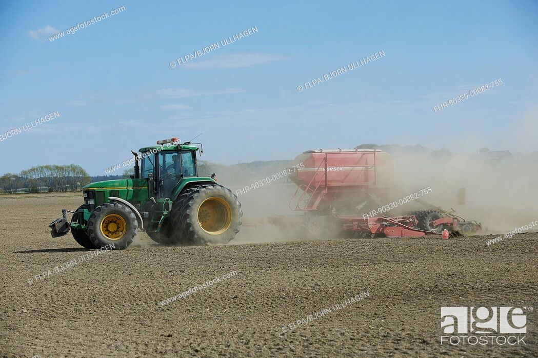 Stock Photo: John Deere 7800 tractor with Horsch seed drill, drilling in dusty arable field, Sweden, April.