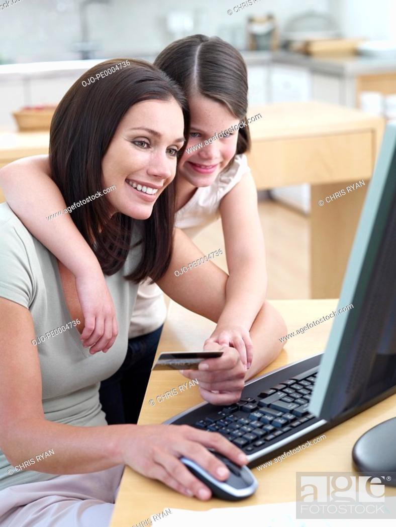 Stock Photo: Woman with credit card on computer with girl.