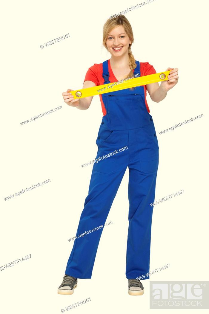 Stock Photo: Young woman holding spirit level, smiling, portrait.