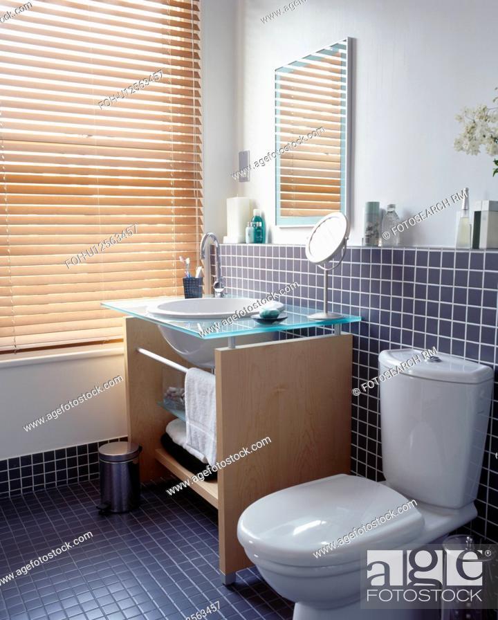 . Basin in wooden vanity unit beside window with slatted blind in