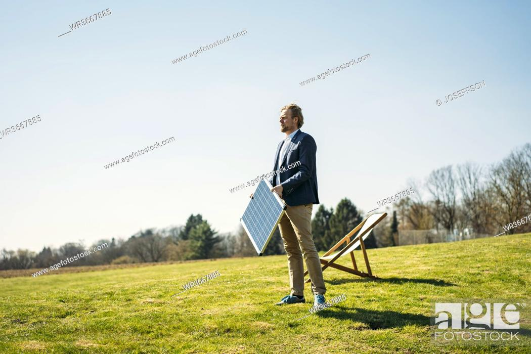 Stock Photo: Businessman looking away while holding solar panel by chair on grass at park against clear sky during sunny day.