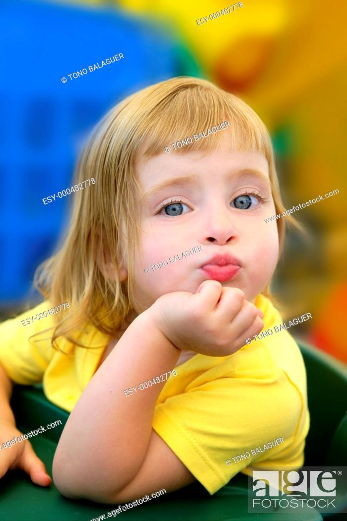 Photo de stock: Blond little girl funny expression in her mouth in colorful background.