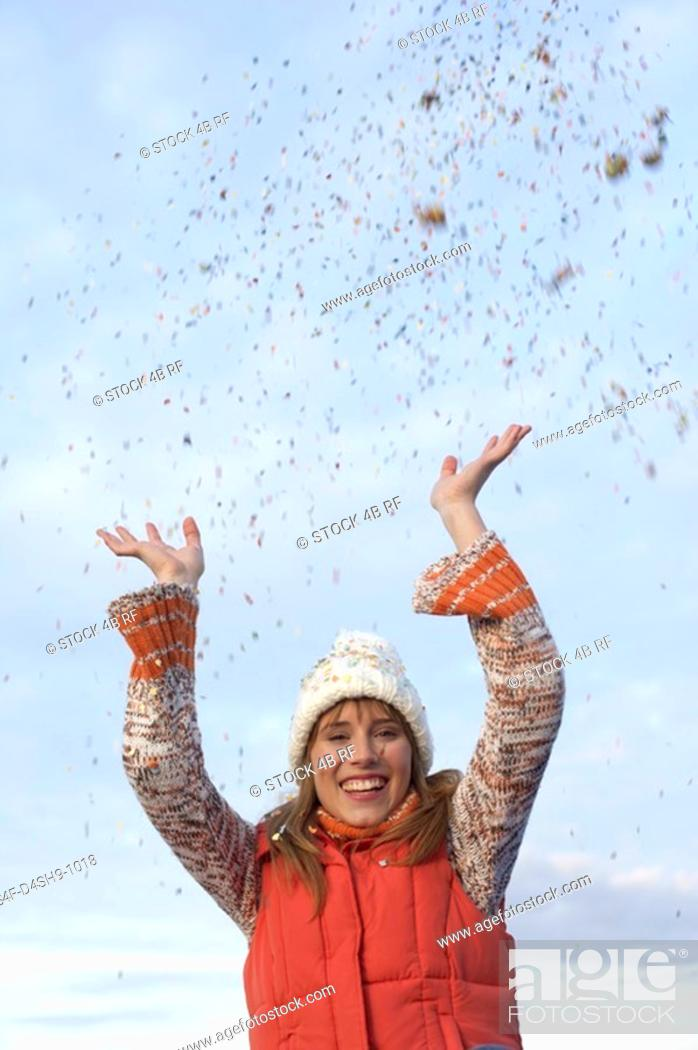 Stock Photo: Young woman with scarf and cardigan under the sky while playing with confetti, close-up.