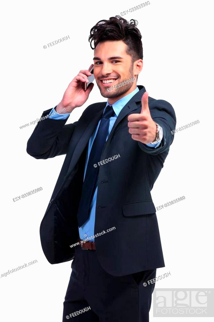 Stock Photo: young business man with very good news on the phone making the ok thumbs up hand gesture.
