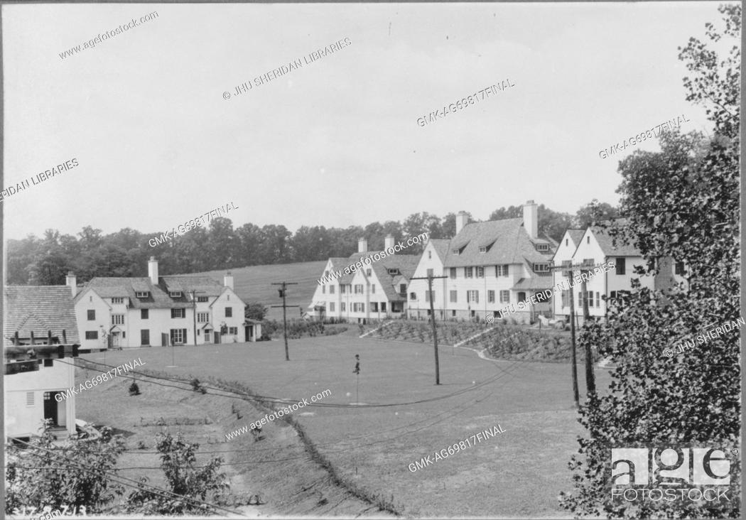 Stock Photo: View of several homes alongside slight hill and grass field with telephone poles, homes are light-colored with many windows and trees around them, Baltimore.