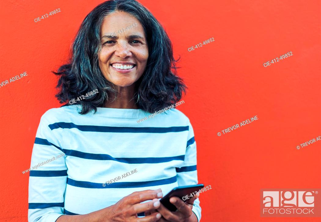 Stock Photo: Portrait smiling, confident woman using smart phone against red background.
