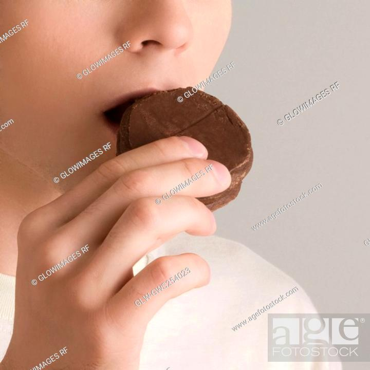 Stock Photo: Close-up of a young woman eating a cookie.