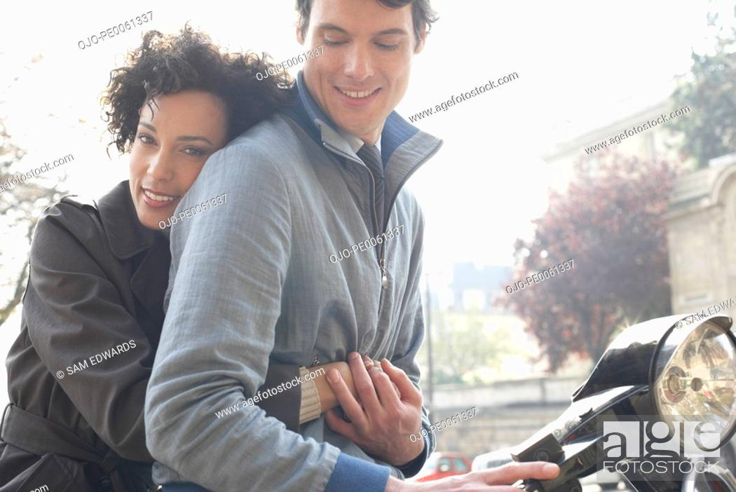 Stock Photo: Couple outdoors on an electric scooter smiling.