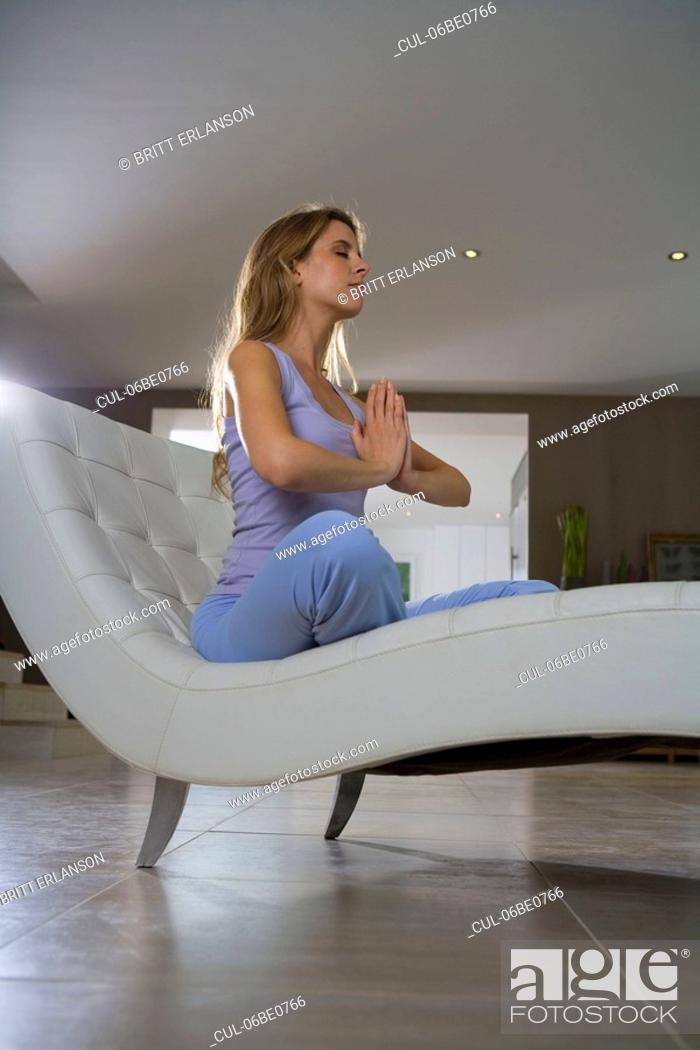 Stock Photo: Woman sitting in yoga position at home.