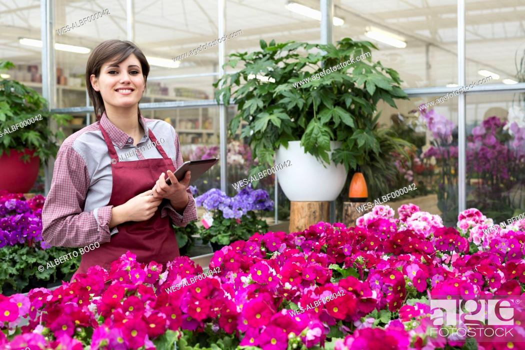 Imagen: Young female gardener working in greenhouse with tablet pc.