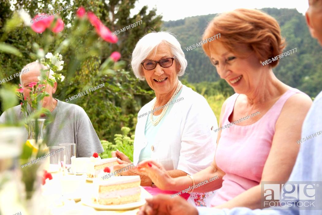 Imagen: Senior ladies eating cake in garden.