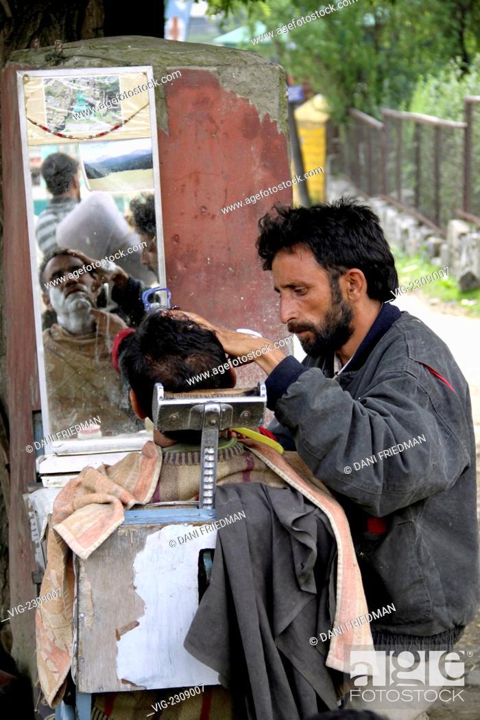 Stock Photo: INDIA, PAHALGAM, 28.06.2010, A Kashmiri roadside barber gives a customer a shave under a tree. - PAHALGAM, KASHMIR, INDIA, 28/06/2010.