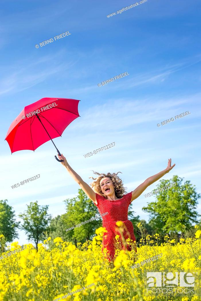 Stock Photo: Carefree woman with arms raised holding umbrella while standing amidst oilseed rapes.