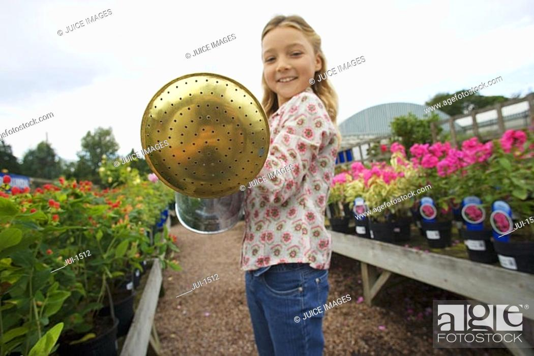 Stock Photo: Blonde girl 7-9 holding watering can in garden centre, smiling, portrait.