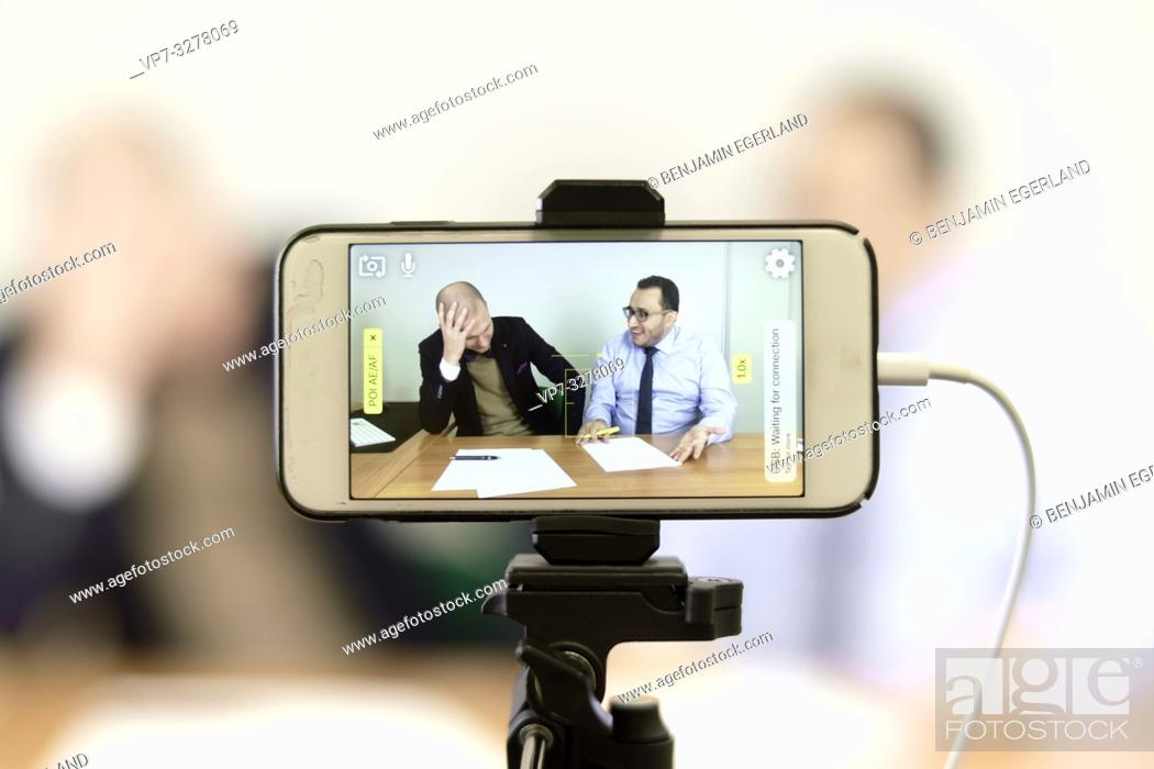Imagen: phone recording live stream video of business men at online conference in office, in Cottbus, Brandenburg, Germany.