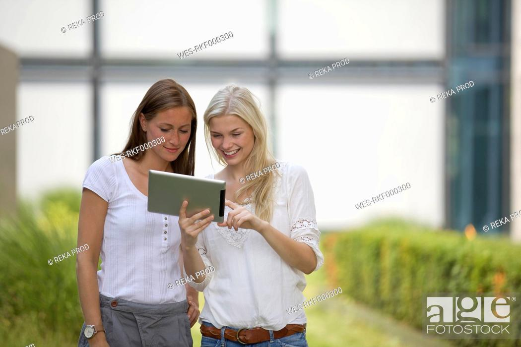 Stock Photo: Germany, North Rhine Westphalia, Cologne, Young students using digital tablet, smiling.